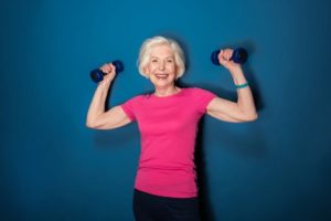 Elderly woman holding a pair of dumbbells.