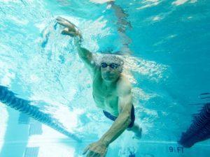 Elderly man swimming.