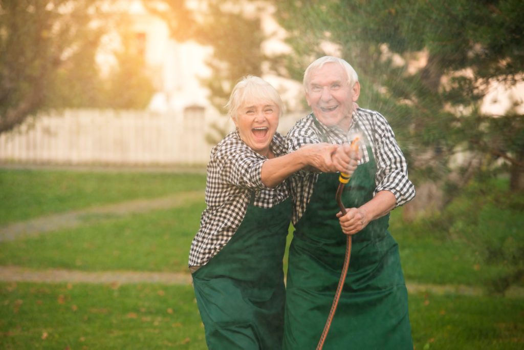 An elderly couple play with a water hose in a yard.