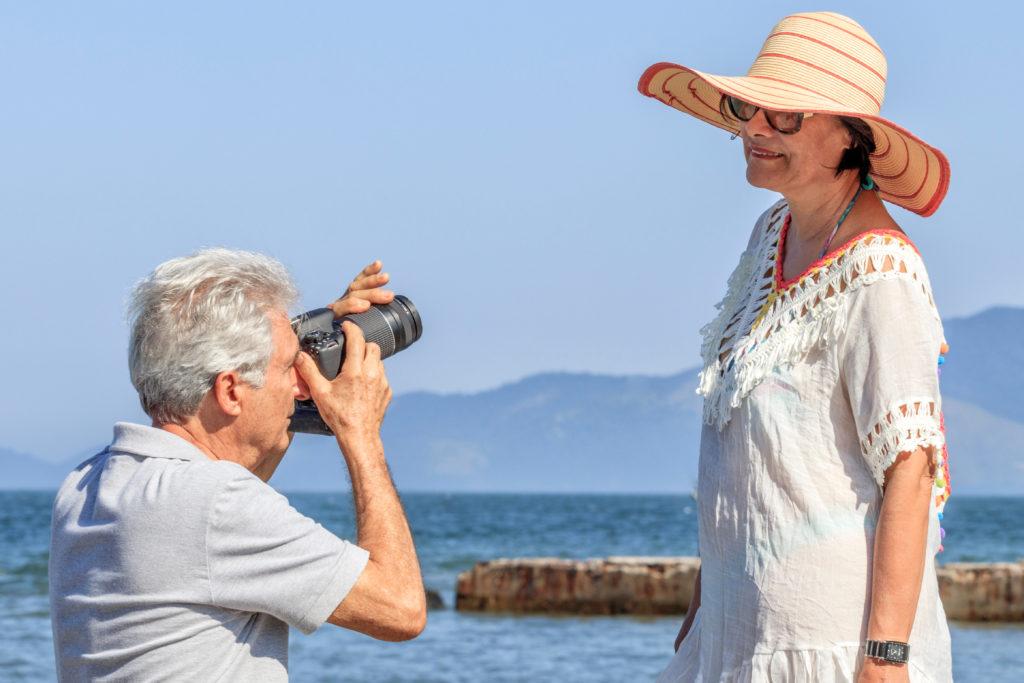 A senior man photographs his wife near the ocean.