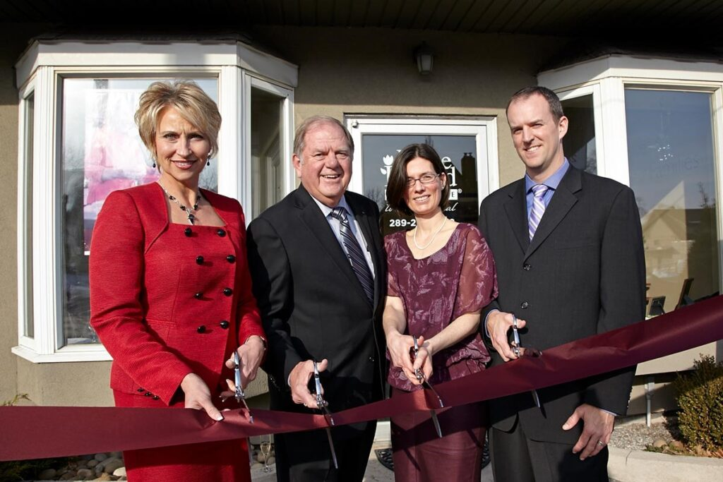 Home Instead franchise business ribbon cutting ceremony with four business people